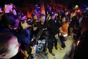 A gathering of people including the media gather around a police officer as he leaves the scene.