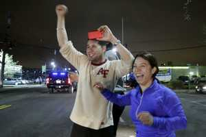 People cheer passing police after the arrest of a suspect.