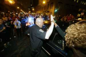 A police officer and a woman react to news of the arrest of one of the Boston Marathon bombing suspects.
