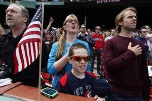 Fans, accompanied by the stadium organist, sing the national anthem before a baseball game between the Boston Red Sox and the Kansas City Royals in Boston, Saturday, April 20, 2013.