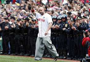 Boston Marathon bombing victim Steven Byrne waves as he comes onto the field for a ceremonial first pitch before a baseball game between the Boston Red Sox and the Kansas City Royals.