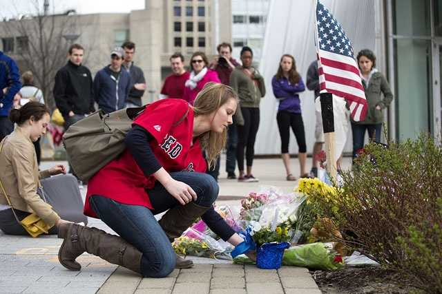 Biology grad student Eleanor Cameron places flowers at the memorial as people gather at a small memorial for slain MIT police officer Sean Collier between the STATA Center and Koch Institute on MIT's campus in Cambridge, Mass., on April 20, 2013.