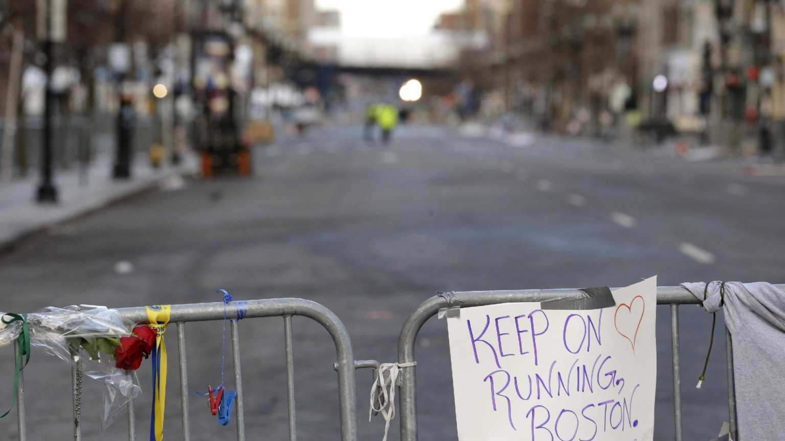 A sign hangs from a barricade on Boylston Street near the finish line of the Boston Marathon.