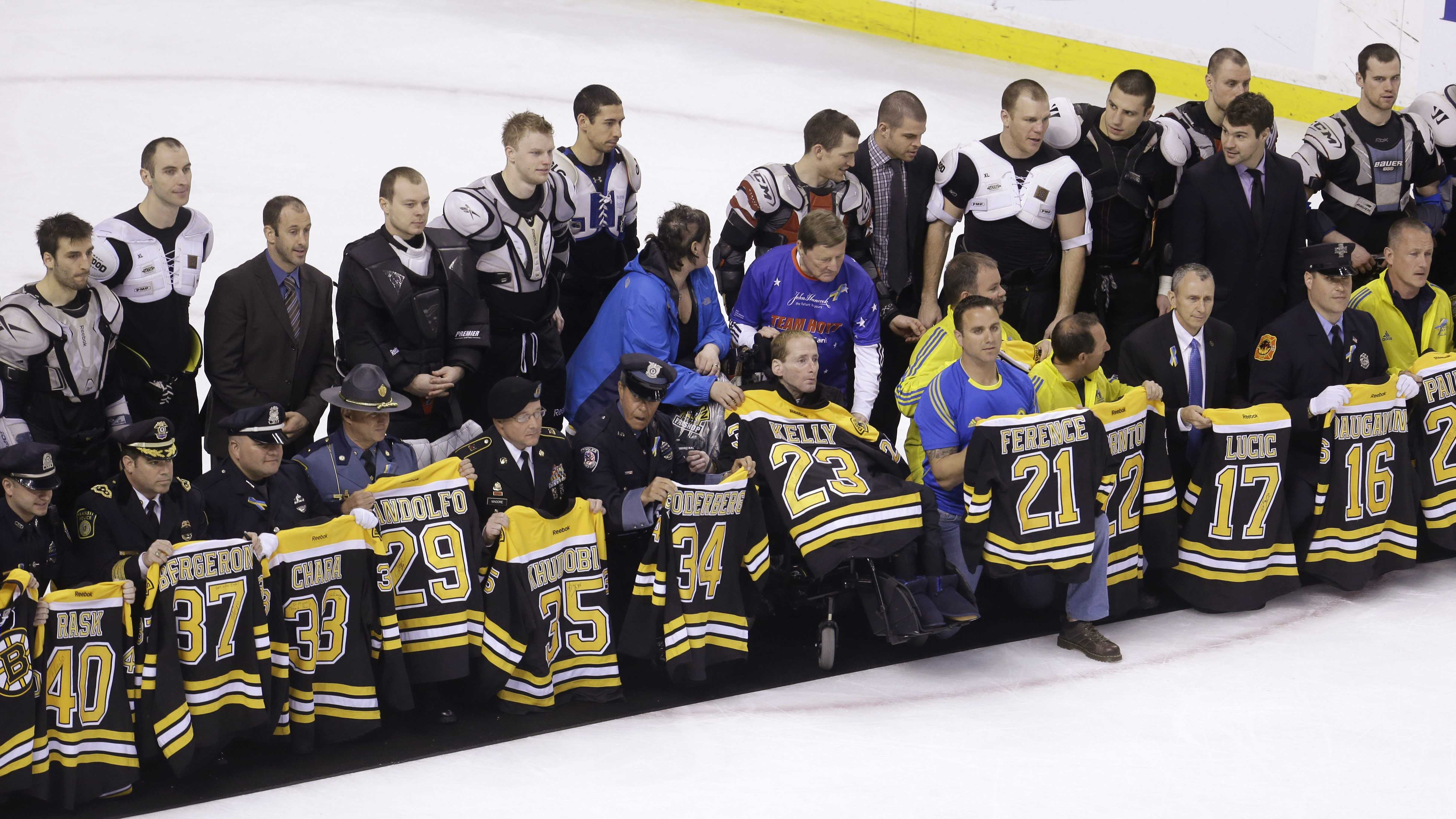 First responders, members of law enforcement and Boston Marathon officials hold Boston Bruins jerseys as they gather with members of the team, back, on the ice following an NHL hockey game against the Florida Panthers at the TD Garden in Boston, Sunday, April 21, 2013.