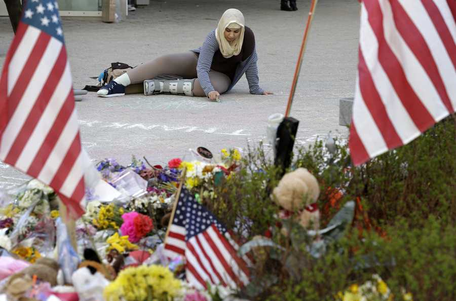 Massachusetts Institute of Technology student Hajar Boughoula of Bizerte, Tunisia, writes a message on the ground with chalk near a makeshift memorial for fallen MIT police officer Sean Collier on the school's campus in Cambridge.