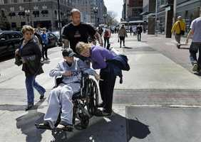 Aaron Hern, 11, of Martinez, Calif. points to the site of the first Boston Marathon bombing to his mother, Katherine, while his father, Alan, wheels him down Boylston Street in Boston's Copley Square, April 25, 2013. Hern was injured during the second bombing at the Boston Marathon finish area on April 15.