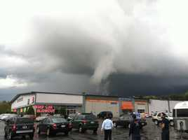 Seng Pell, a salesman at the Baystate Ford Pre-owned Center on Washington Street, told customers to get away from the windows as a funnel cloud moved through and damaged a garage door and some vehicles at the shop.