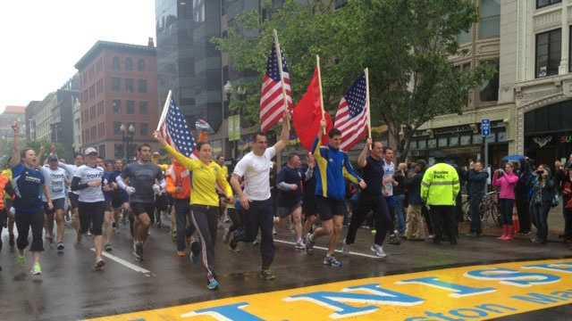 Runners cross the Boston Marathon finish line in the OneRun on Saturday, May 25, 2013.
