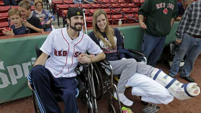 In this Thursday, May 23, 2013 photo, Boston Marathon bombing survivor Pete DiMartino, of Rochester, N.Y., and his girlfriend, Rebekah Gregory, hold hands prior to DiMartino throwing out the ceremonial first pitch before a Red Sox game at Fenway Park.