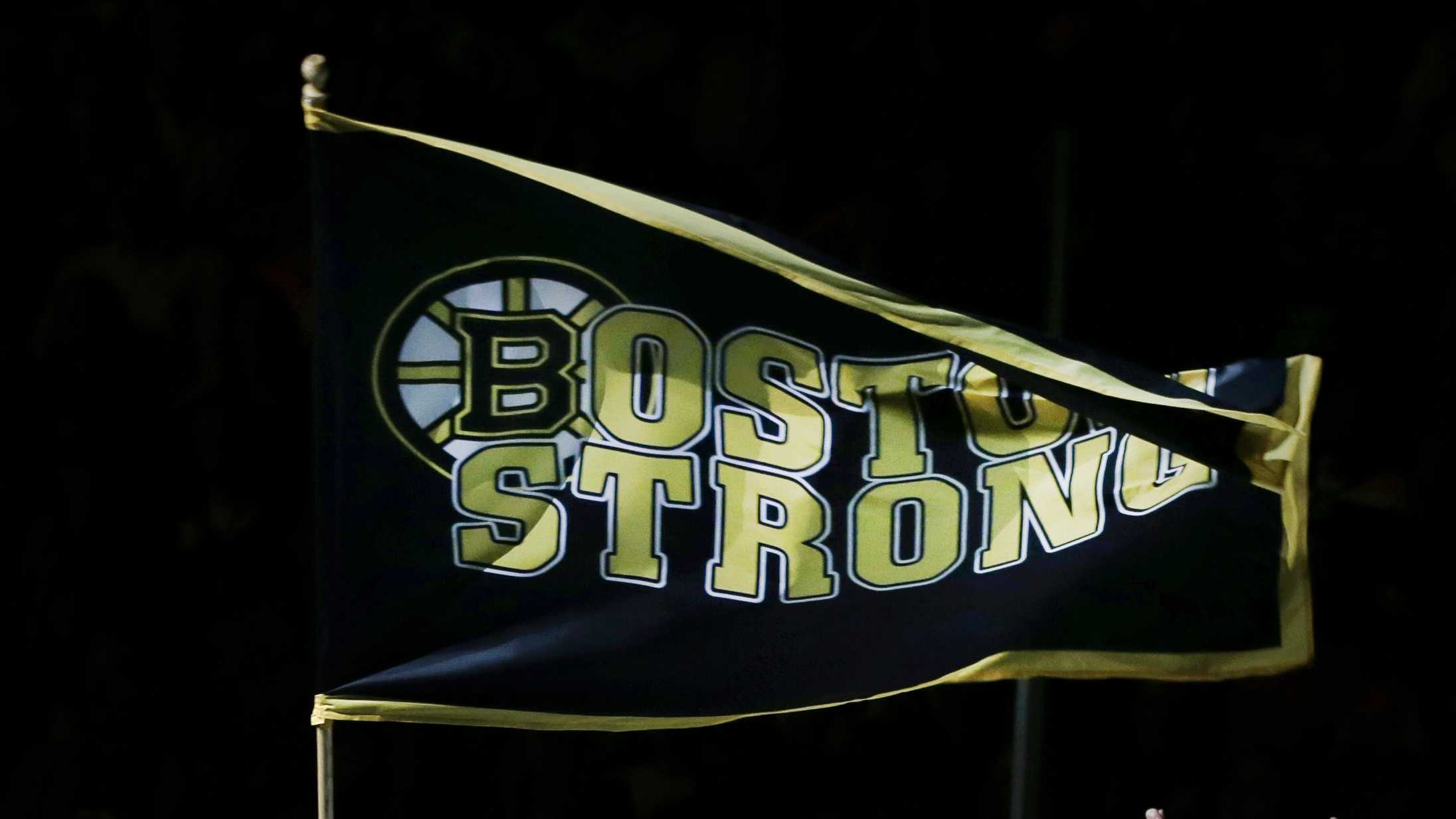 "Richard Donohue, the Massachusetts Bay Transportation Authority officer wounded during the shootout with the Boston Marathon bombing suspects, waves a ""Boston Strong"" banner as his wife, Kimberly, raises her arms during ceremonies prior to Game 3 of the Eastern Conference finals in the NHL hockey Stanley Cup playoffs between the Boston Bruins and the Pittsburgh Penguins, in Boston on Wednesday, June 5, 2013."