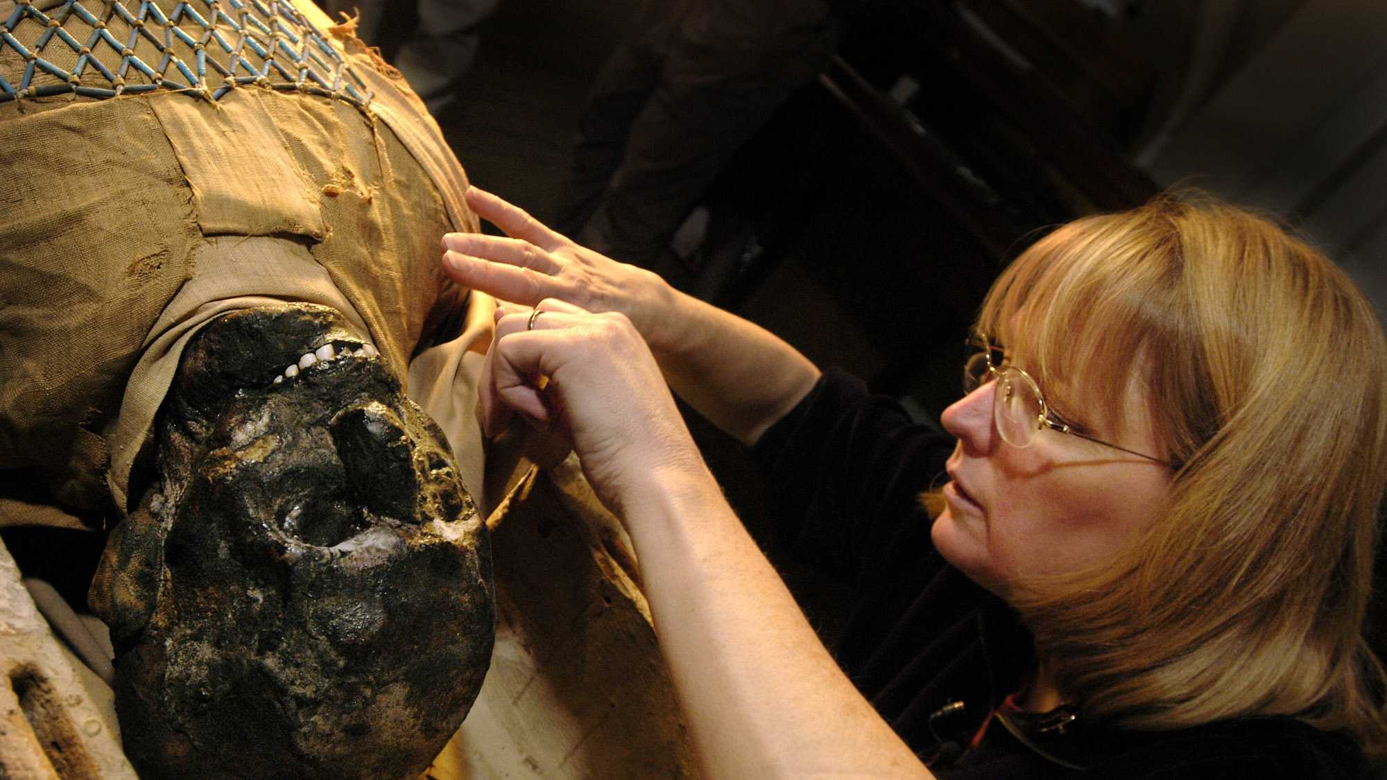 Egyptologist Mimi Leveque begins to remove the protective wrappings around a 2,500 year-old mummy at Massachusetts General Hospital in Boston.