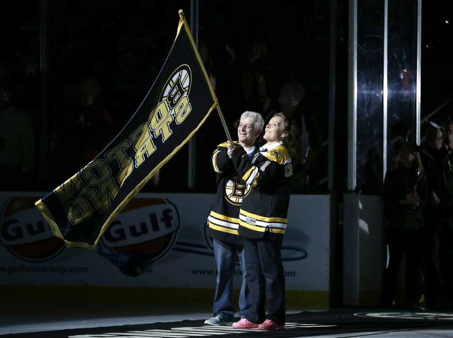 """William and Patricia Campbell, parents of Krystle Campbell, who was killed in the Boston Marathon bombings, wave a """"Boston Strong"""" banner before Game 4 in the Eastern Conference finals of the NHL hockey Stanley Cup playoffs between the Boston Bruins and the Pittsburgh Penguins, in Boston on Friday, June 7, 2013."""