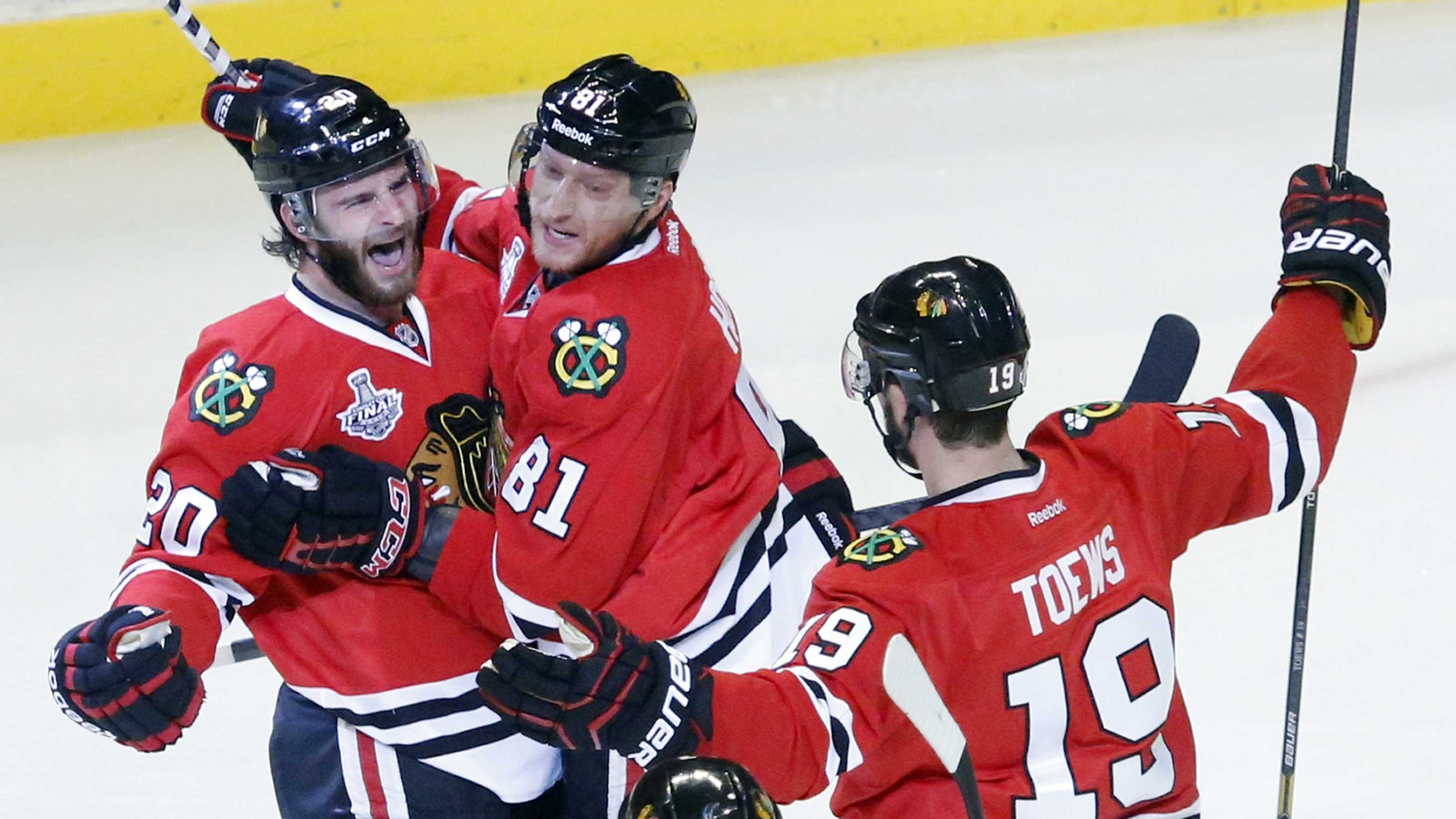 Chicago Blackhawks left wing Brandon Saad (20) celebrates with right wing Marian Hossa (81) and center Jonathan Toews (19) after scoring a goal during the second period of Game 1 in their NHL Stanley Cup Final hockey series against the Boston Bruins, Wednesday, June 12, 2013, in Chicago.