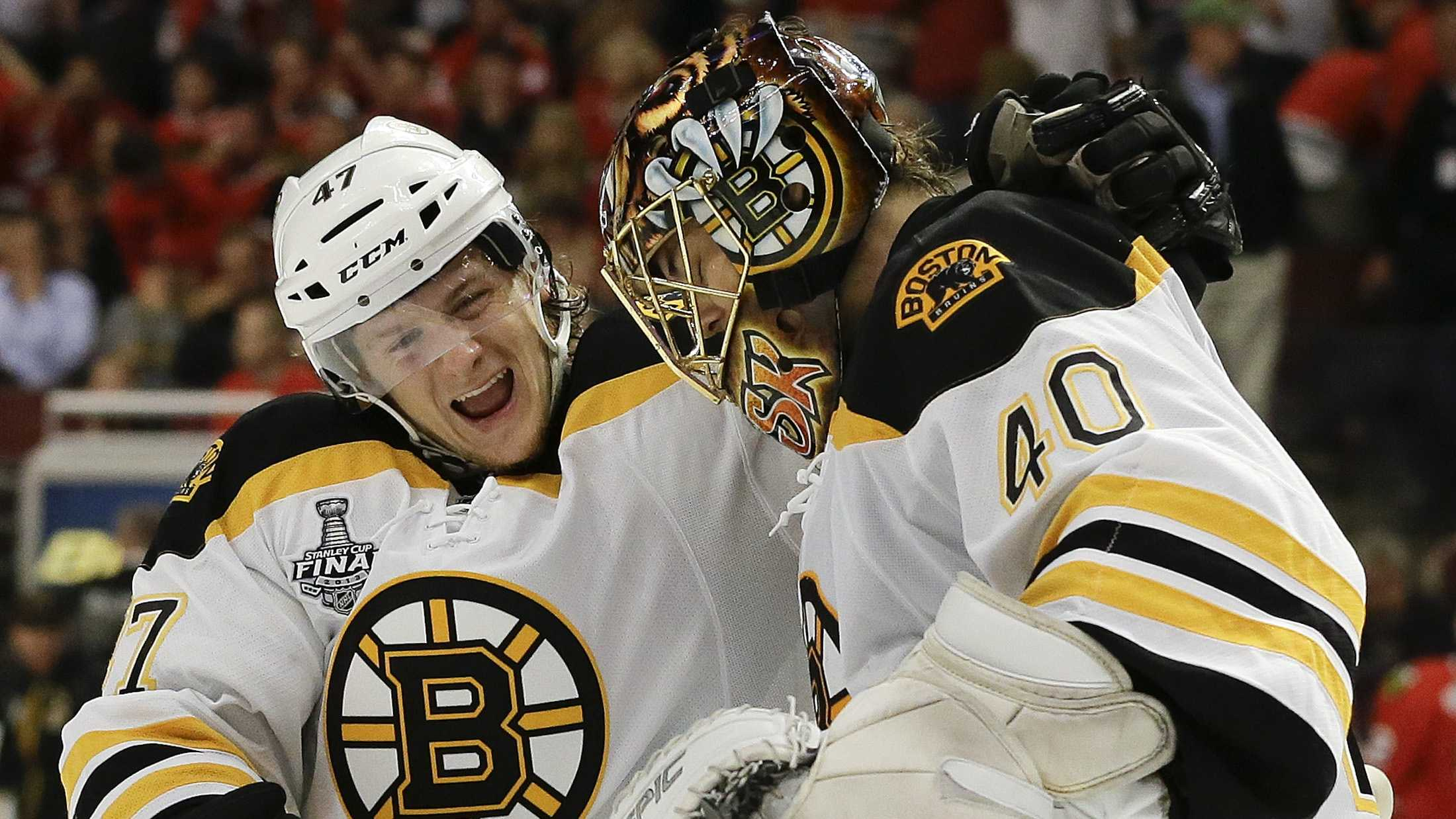 Boston Bruins defenseman Torey Krug (47) celebrates with goalie Tuukka Rask (40) after the Bruins scored a goal against the Chicago Blackhawks in sudden death overtime during Game 2 of the NHL hockey Stanley Cup Finals, Saturday, June 15, 2013, in Chicago. The Bruins won 2-1.