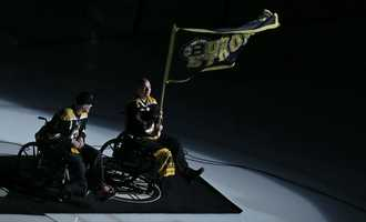 """Boston Marathon bombing survivor Paul Norden, of Stoneham, Mass. waves a """"Boston Strong"""" flag from the ice with his brother J.P. Norden, also a bombing survivor, before the Boston Bruins face the New York Rangers in Game 5 of the Eastern Conference semifinals in the NHL hockey Stanley Cup playoffs in Boston, Saturday, May 25, 2013."""