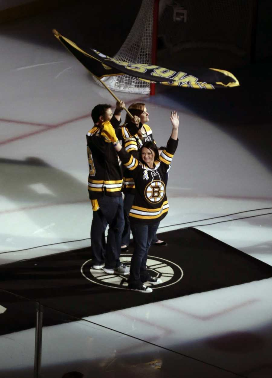 Rob Rogers, Jenn Rogers, and Jennifer Lemmerman, wave a Boston Strong banner before Game 3 of the NHL hockey Stanley Cup Finals between the Boston Bruins and the Chicago Blackhawks in Boston, Monday, June 17, 2013. The three are relatives of MIT police officer Sean Collier, killed during confrontation with suspects in the Boston Marathon bombing on April 15.