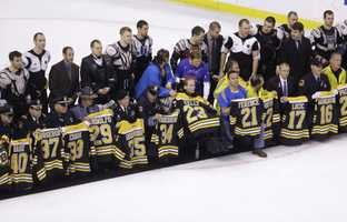 First responders, members of law enforcement and Boston Marathon officials hold Boston Bruins jerseys as they gather with members of the team, back, on the ice at the TD Garden in Boston, Sunday, April 21, 2013. In a change requested by fans, Bruins players presented their jerseys to some of those who offered help in the minutes and days following the marathon bombings on Monday.