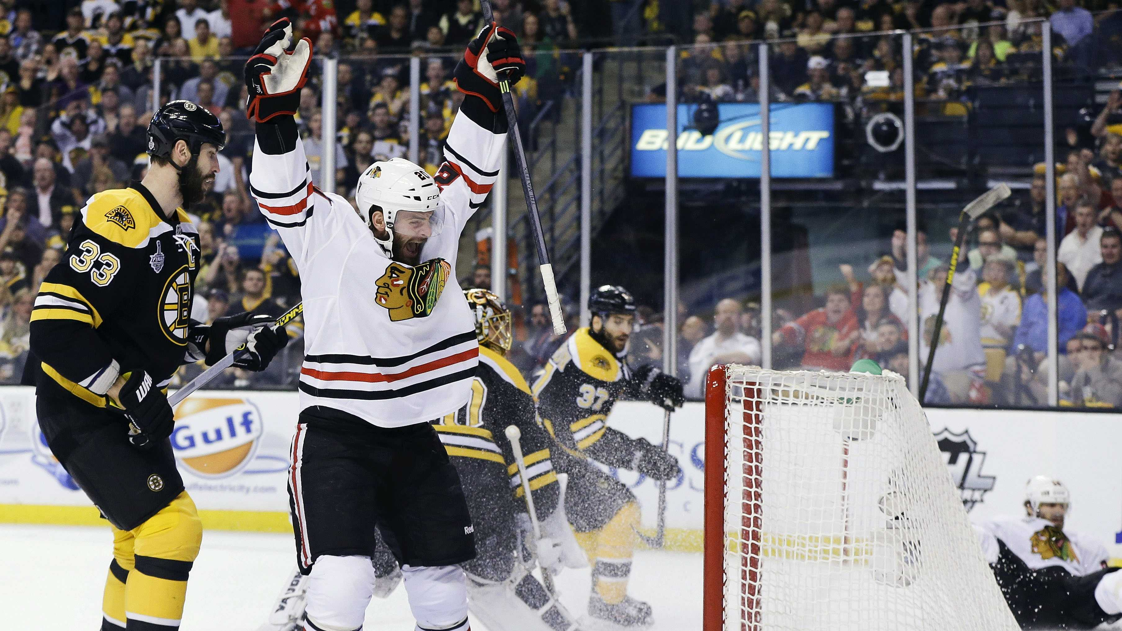 Chicago Blackhawks left wing Brandon Saad, center, celebrates a goal by Blackhawks center Michal Handzus, right, in front of Boston Bruins defenseman Zdeno Chara (33) during the first period in Game 4 of the NHL hockey Stanley Cup Finals, Wednesday, June 19, 2013, in Boston.