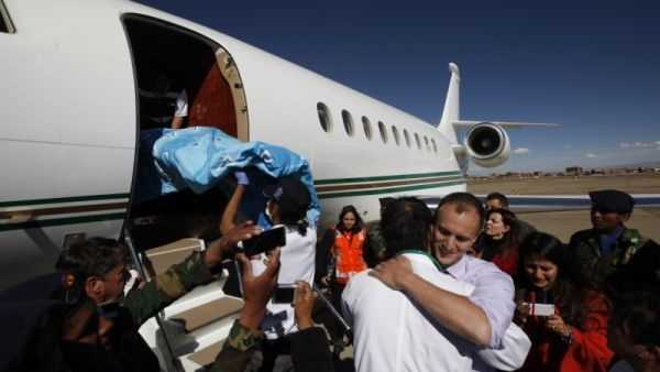 Dr. Joseph Currier, right, facing camera, embraces a Bolivian doctor, as a stretcher carrying four-year-old Rosalie is placed into a private plane at the airport in El Alto, Bolivia, Thursday, June 20, 2013.