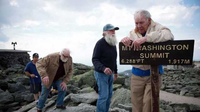 In this June 1, 2013 photo, Guy Gosselin, left, makes his way to the summit of Mount Washington to reunite with Gerry Wright, center, and Harold Addison, right, in Gorham, N.H. Gosselin, who was working at the observatory atop the mountain, helped Wright and Addison, who needed food and shelter from the cold and high winds during their summit attempt 50 years ago.