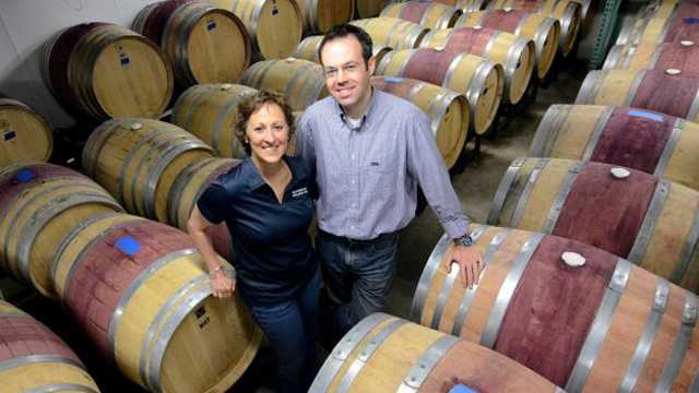 In this June 7, 2013 photo, Donna and Christian Hanson pose with wine casks at Balderdash Cellars in Pittsfield, Mass. The couple started in the basement of their house, then moved to the garage, then moved to the basement of a former bakery on East street.