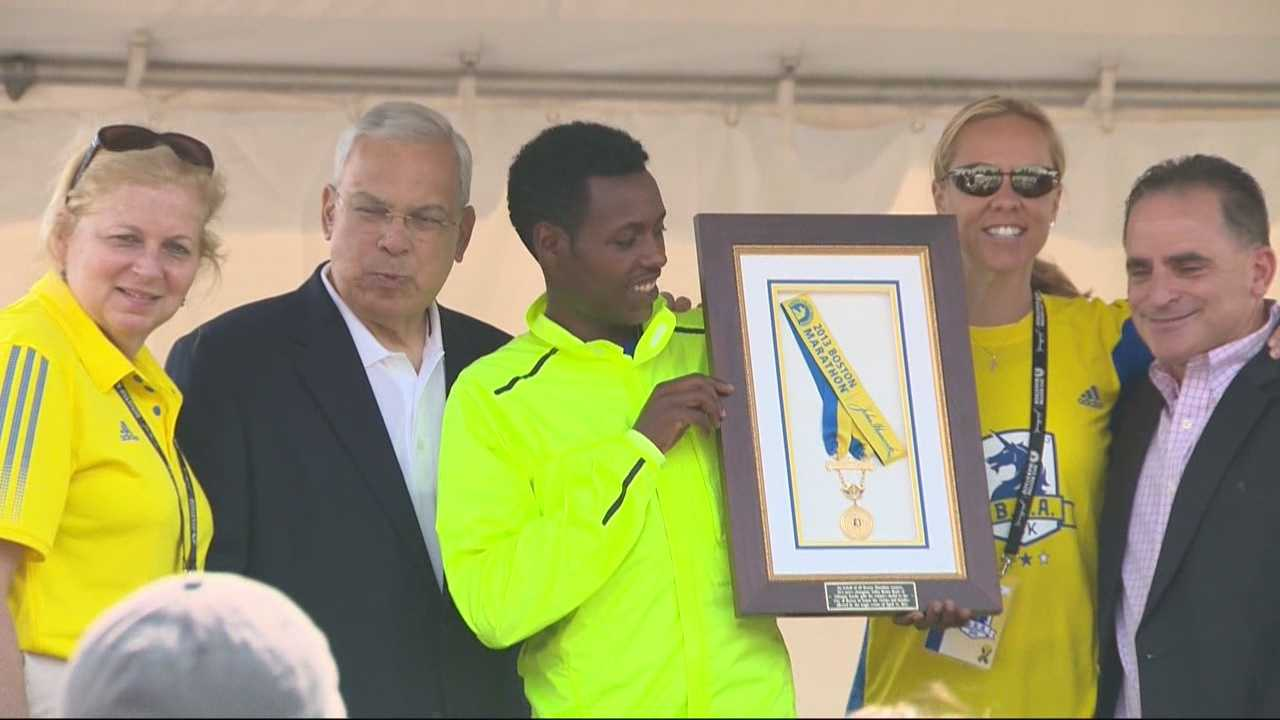 Lelisa Desisa presents his 2013 medal to Mayor Tom Menino at a ceremony on the Boston Common.