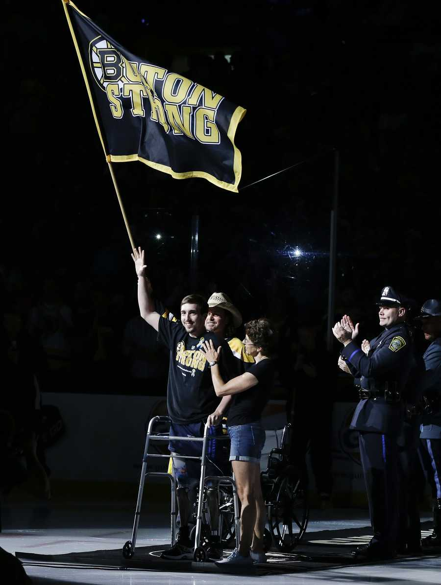 Standing on artificial legs, Boston Marathon bombing victim Jeff Bauman and Carlos Arredondo, wearing the hat, who assisted him at the scene, waves the Boston Strong banner before Game 6 of the NHL hockey Stanley Cup Finals between the Boston Bruins and the Chicago Blackhawks, Monday, June 24, 2013, in Boston.