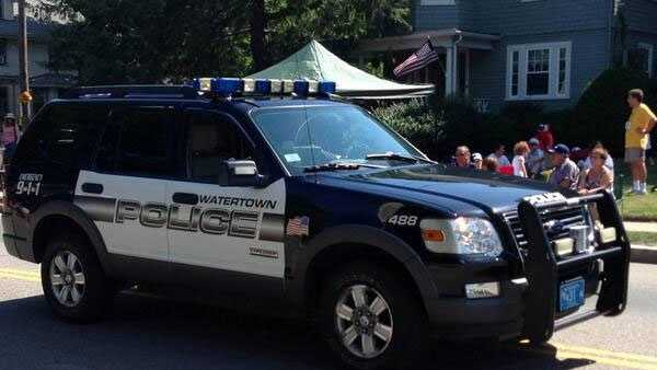 A Watertown police cruiser rides in the 2013 July 4th parade in Needham.