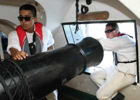 Members of the USS Constitution load the guns below deck for firing.