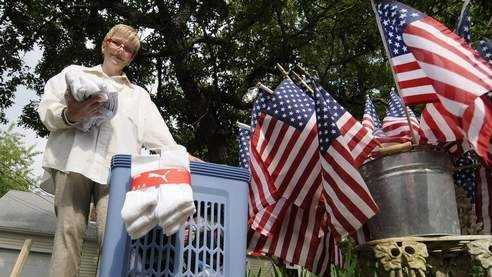 Maureen Tuohy-Bedford stands by her sock drop-off bin that she has set up at the end of her driveway at her West Yarmouth Road home.