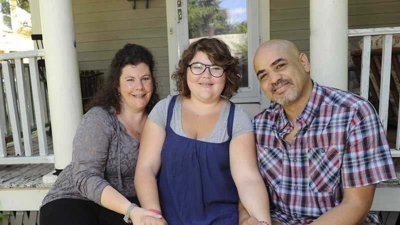 In this June 20, 2013 photo, Becky Bluh, left, and Tony Derricotte pose for a photo with their daughter, Cameron Bluh-Derricotte, center, at their home in Greenfield, Mass. The Make-A-Wish Foundation has arranged a trip to London for Cameron, who has a rare autoimmune disorder.