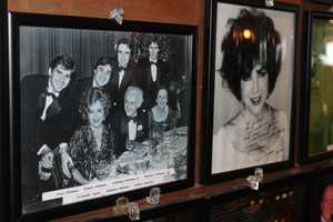 The Athanas family posed for a picture with Elizabeth Taylor on one of her many visits to the restaurant. Ms. Taylor liked the chairs in the dining room so much, that Anthony Athanas sent 12 of them to her home in Switzerland. She was seen sitting in one of them during an interview on national television.