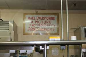 """This sign, which reads, """"Make Every Order A Picture, If Not Proud Of It, Don't Serve It!"""" hung in the back of the kitchen, reminding the kitchen staff to pay careful attention to the dishes they prepared"""