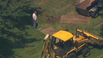 A backhoe was brought in to break into the ground and help grave diggers.