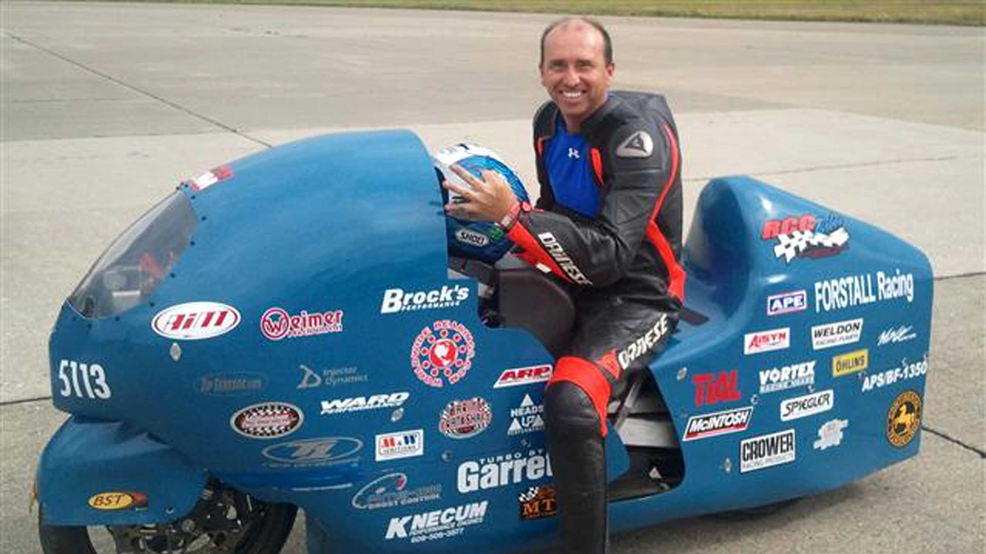 In this 2011 photo provided by the Loring Timing Association the late Bill Warner, 44, of Wimauma, Fla., holds his helmet while sitting on a motorcycle.