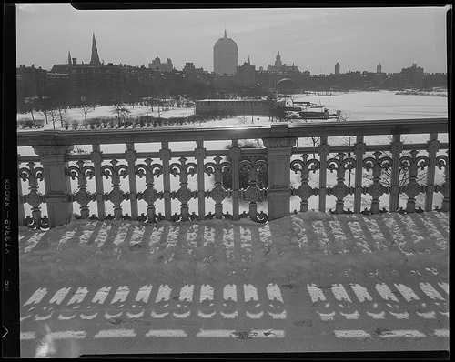 A snowy view of the iron railing and Boston skyline in the Back Bay from the Longfellow Bridge. Taken between 1934-1956