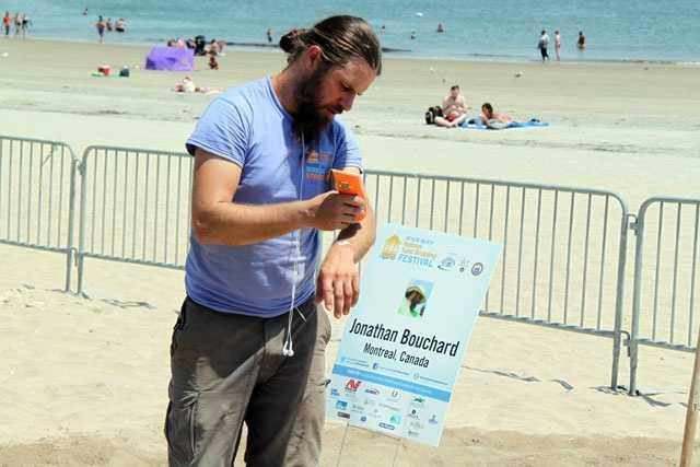 Sculptor Jonathan Bouchard applies sunscreen.