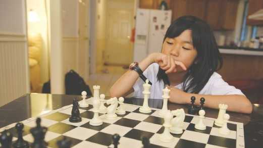 Carissa Yip, 9, considers her next move on the chessboard.