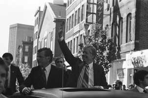 President Jimmy Carter, accompanied by Sen. Edward Kennedy, left, waves to the crowd as his motorcade passes through the North End during a campaign trip, Oct. 16, 1980.