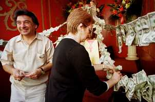 """Sandra DiMuzio, of Plainville, Mass., center, attaches dollar bills to ribbons draped on a statue of St. Anthony as Joe Romano, of Burlington, Mass., looks on during a """"St. Anthony's Feast"""" celebration in Boston's North End neighborhood, Sunday, Aug. 29, 1999."""