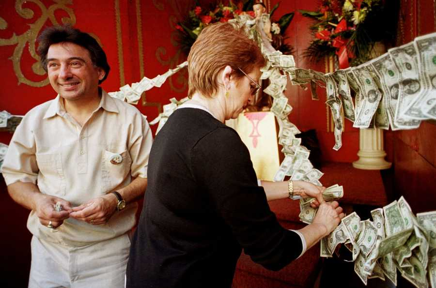 "Sandra DiMuzio, of Plainville, Mass., center, attaches dollar bills to ribbons draped on a statue of St. Anthony as Joe Romano, of Burlington, Mass., looks on during a ""St. Anthony's Feast"" celebration in Boston's North End neighborhood, Sunday, Aug. 29, 1999."