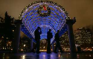Sightseers walk past a trellised arch adorned with holiday lights at Christopher Columbus Park in the North End neighborhood of Boston, Dec. 1, 2006.