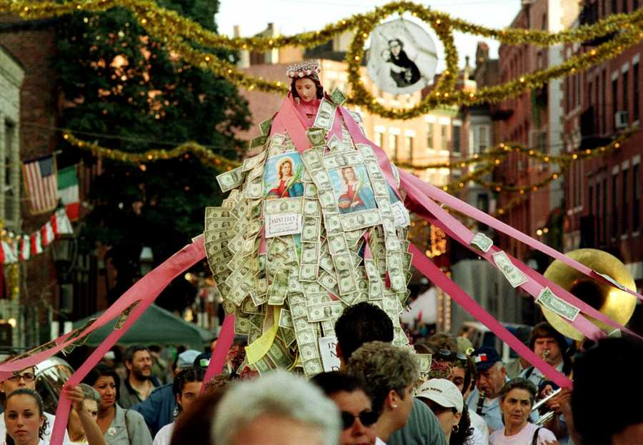 Saint Lucy, patron saint of eyes, is carried through the streets of Boston's North End neighborhood, Monday, Aug. 28, 2000. Supported by women during the procession, the statue is gradually covered by cash donations offered by local residents.