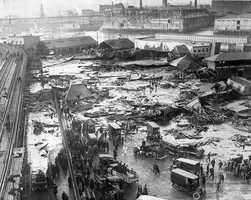 This aerial view shows the site of the molasses storage tank explosion in the section of Commercial St. between Copps Hill and the playground of North End Park, Jan. 15, 1919. The explosion of the steel vat, ninety feet in diameter and fifty-two feet in height, caused 2.2 million gallons of molasses to flood the area, killing 21 people and injuring 150. In the background is the Navy Yard in Charlestown.