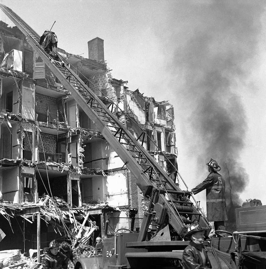 Firefighters use a building being demolished in Boston's West End section as a backdrop for a civil defense test, May 3, 1960.