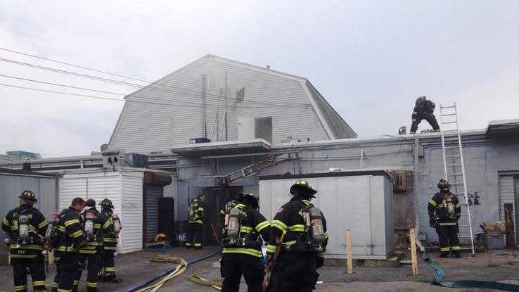 Abington firefighters at the scene of a two-alarm fire at the Terra Nossa Center Market on Saturday, Aug. 3, 2013.