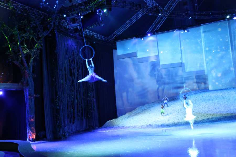 Acrobats hang from the ceiling over the lake for their closing performance