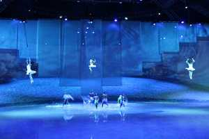 The performers swing back and forth above the water