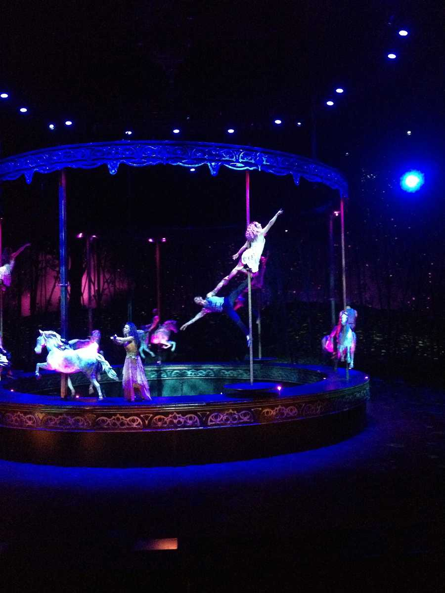 A carousel drops down to the stage where acrobats perform on its spinning poles