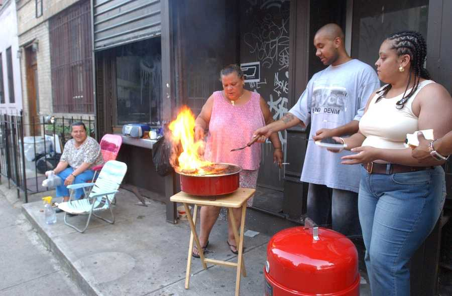Members of the Ortiz Family have a barbecue in front of their building on East 11th Street after a power blackout in New York City disabled their electric stove, Thursday, Aug. 14, 2003.